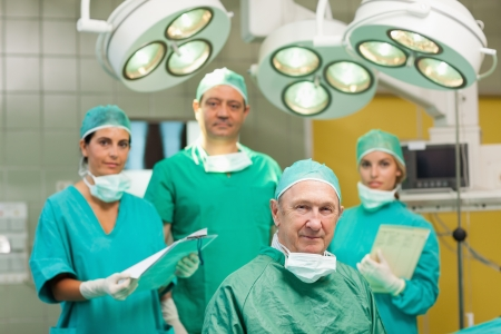 operation gown: Smiling surgeon sitting with a team behind him in a surgical room