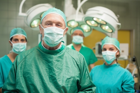 doctor examining woman: Smiling surgeon posing with a team in a surgical room Stock Photo