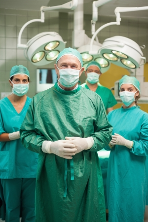 Smiling surgeon posing with a  medical team in a surgical room photo