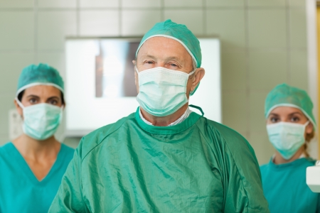 operation gown: Surgeon with two interns behind him in a surgical room Stock Photo