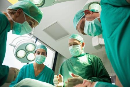 operation gown: Equipo quir�rgico trabaja en un paciente sangrado en una sala quir�rgica Foto de archivo