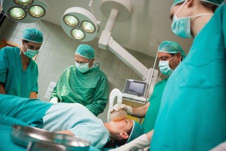 operation gown: Cirujano sosteniendo una m�scara en la cara de una mujer en una sala de operaciones