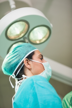 surgical light: Woman surgeon under a surgical light in a surgical room