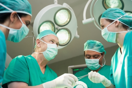 Surgeon team working together in a surgical room photo