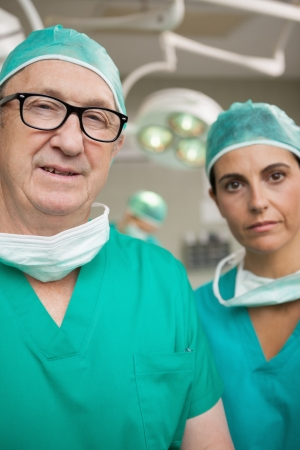 Surgeon with glasses on and a colleague in a surgical room photo