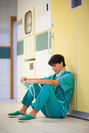 Woman surgeon sitting in a hallway photo