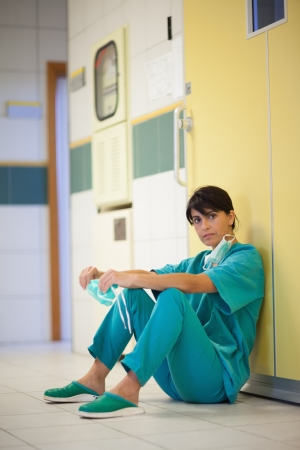 Surgeon sitting on the floor in a hallway photo