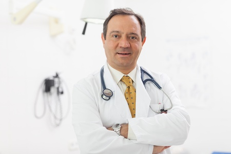 Doctor crossing his arms while smiling in an examination room Stock Photo - 16202110
