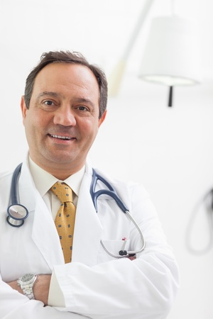 Smiling doctor folding his arms in an examination room Stock Photo - 16202305