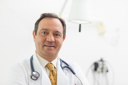 Doctor smiling with a stethoscope around his neck in an examination room Stock Photo - 16202222