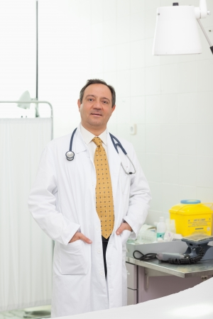 Doctor with his hands in his pockets in an examination room photo