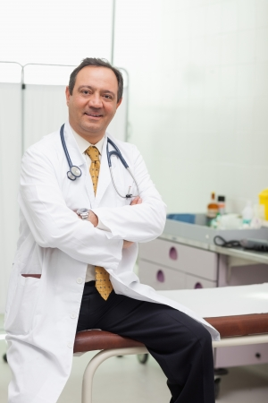 Doctor smiling while sitting on a table in an examination room Stock Photo - 16203040