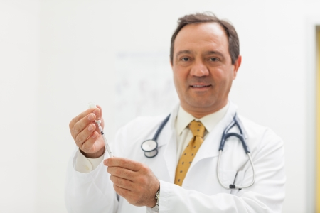 Smiling doctor preparing a syringe in an examination Stock Photo - 16201996
