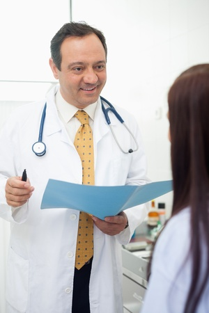 Smiling doctor talking to his patient in an examination room Stock Photo - 16203142