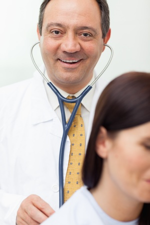 Smiling doctor auscultating a patient in an examination room Stock Photo - 16203751
