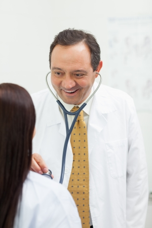 Smiling doctor auscultating a woman in an examination room Stock Photo - 16203147