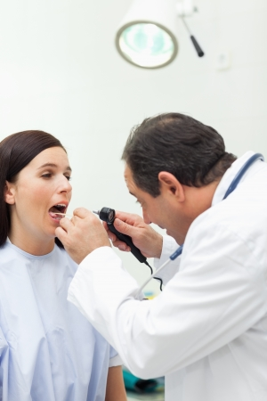 Doctor auscultating the mouth of his patient in an examination room Stock Photo - 16203206