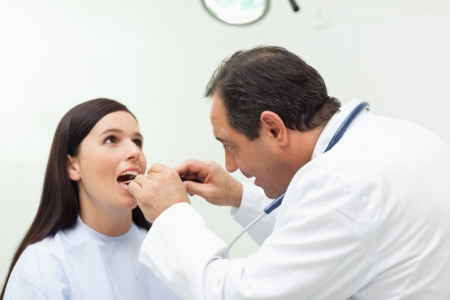 Doctor looking at the mouth of his patient in an examination room Stock Photo - 16202730