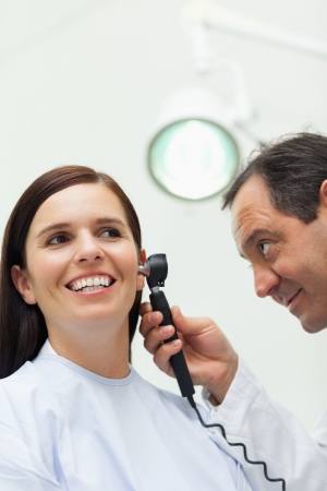 Doctor using an otoscope to look at the ear of a patient in an examination room Stock Photo - 16203558
