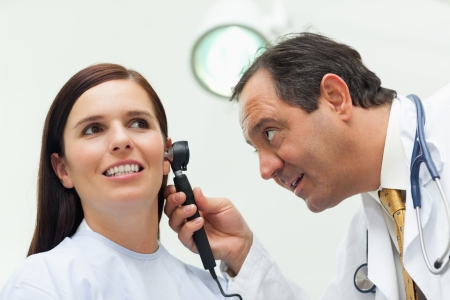 Doctor using an otoscope to look at the ear of his patient in an examination room photo
