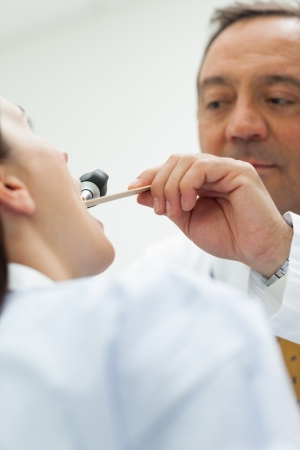 Doctor auscultating the mouth of a patient in an examination room Stock Photo - 16203105