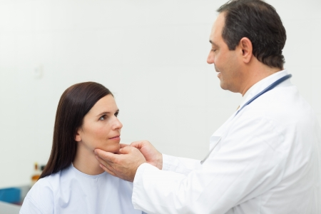 groping: Doctor auscultating the neck of a patient in an examination room