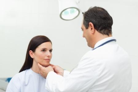 Doctor auscultating the neck of his patient in an examination room photo