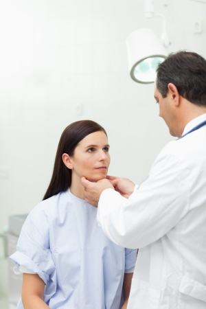 groping: Doctor touching the neck of a patient in an examination room