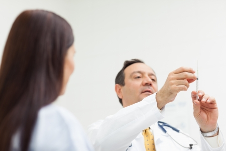 Doctor checking an injection for a patient in an examination room photo