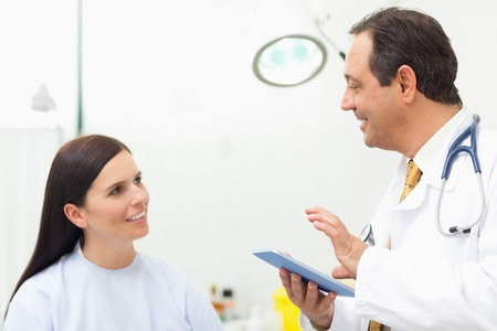 Doctor talking to a patient while holding a tablet tactile in an examination room Stock Photo - 16202088