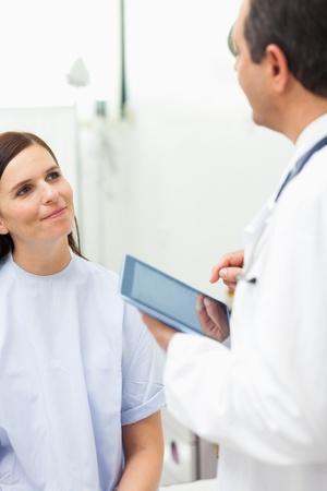 Frau h�rt zu einem Arzt in einem Untersuchungsraum