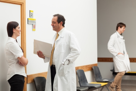 Doctors and a patient talking in an hospital hallway Stock Photo - 16202978