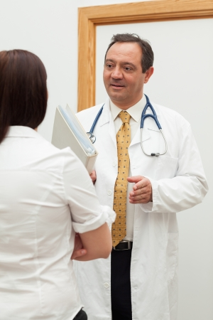 Doctor holding files while talking to a patient in a hallway photo