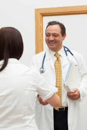 Doctor shaking the hand of a patient while holding a file in a hallway photo