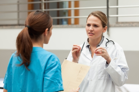 Doctor explaining something to someone in a hallway photo