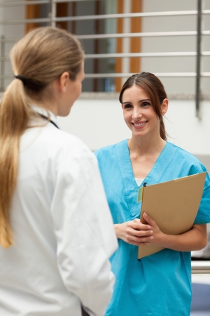 Smiling nurse talking to a doctor in a hospital reception Stock Photo - 16206960
