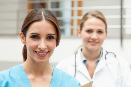 Smiling nurse and doctor standing in a hospital reception photo