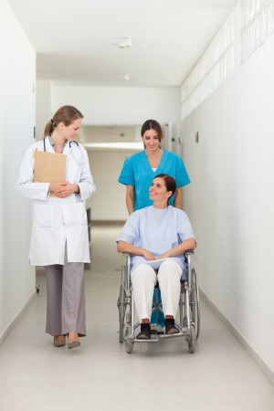 Nurse pushing a patient in a wheelchair while talking to a doctor in a hospital hallway Stock Photo - 16203897