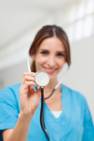 Smiling nurse holding a stethoscope in a hallway Stock Photo - 16203545