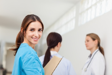 Smiling nurse  while standing in a hallway with a patient and a doctor in a hallway photo