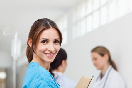 Smiling woman  while standing in a hallway with a patient and a doctor in a hallway photo