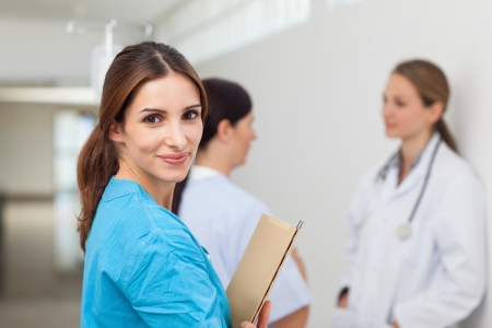 Nurse in a hallway with a doctor and a patient while holding files in a hospital photo