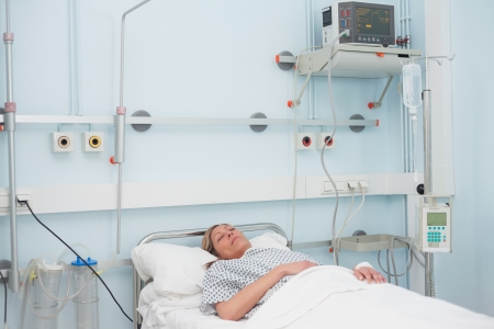 recuperation: Female patient lying on a bed in hospital ward