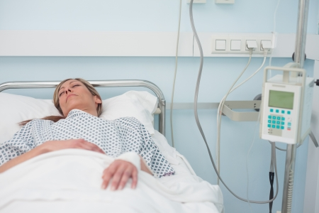 Woman sleeping on a medical bed in hospital ward photo