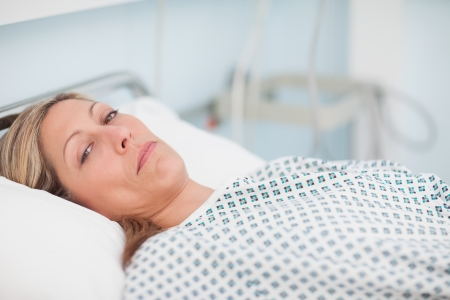 recuperation: Female patient looking at camera in hospital ward