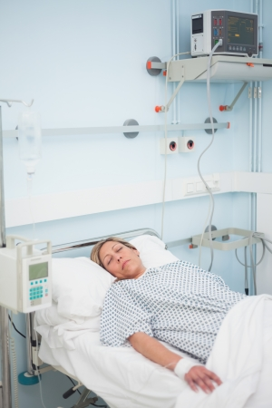 Woman lying on a bed with closed eyes in hospital ward photo