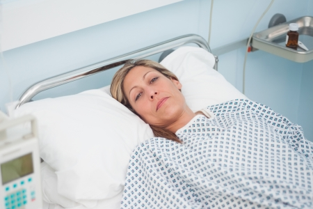 Woman lying on a bed while looking at camera in hospital ward Stock Photo - 16201460