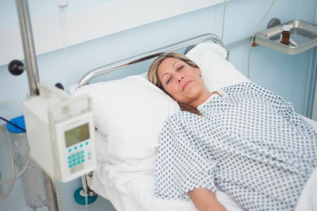 Female patient lying on a bed while looking at camera in hospital ward Stock Photo - 16204863