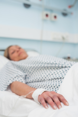 woman bed: Centrarse en la mano de un paciente acostado en una cama m�dica en sala de hospital