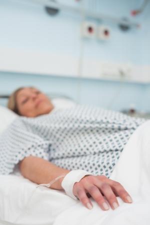 Konzentrieren Sie sich auf die Hand eines Patienten liegt auf einem Krankenbett in Krankenstation